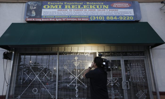 "A news television cameraman tapes ""Santeria"" motifs decorating the exterior window of a botanica called Omi Relekun in Compton, Calif., on Jan. 22, 2016. L.A. County sheriff's Capt. Steve Katz says deputies responded to the shop that sells spiritual items after a woman complained of animal cruelty. Katz says they found a skull inside a pot and eight other pots that may also contain skulls. Katz says there's no evidence of a homicide and that it appears the skull may have been purchased from a legal source and was being used for a religious ceremony. He says it's unclear whether animal remains were found. (AP Photo/Damian Dovarganes)"