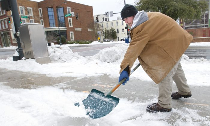 Chase Coble works a snow shovel on West Washington Street as city crews worked to clear downtown streets and sidewalks in the aftermath of the winter storm, on Saturday, Jan. 23, 2016, in Greensboro, N.C. (Joseph Rodriguez/News & Record via AP)