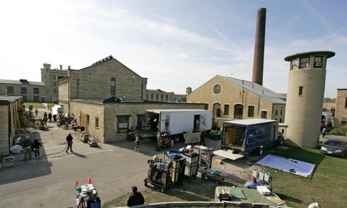 """Film trucks and crew wait behind storage buildings at the Joliet Correctional Center in Joliet, Ill, Oct. 19, 2005, where about half of the scenes on the Fox series """"Prison Break"""" are filmed. (AP Photo/M. Spencer Green)"""