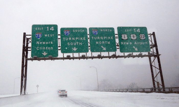 A vehicle drives on the I-78 extension of the New Jersey Turnpike during a snowstorm, Saturday, Jan. 23, 2016, in Newark, N.J. Towns across the state are hunkering down during a major snowstorm that hit overnight. (AP Photo/Julio Cortez)