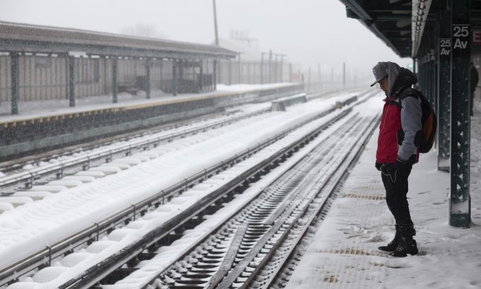 A man waits for a D train at the snow-covered 25th Avenue stop in the Brooklyn borough of New York on Saturday, Jan. 23, 2016, in New York. Service at above-ground stations was suspended later in the day due to a blizzard. (AP Photo/David Boe)