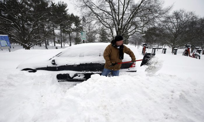 Jared Meyer of Chattanooga, Tenn., digs out his car from the snow, Saturday, Jan. 23, 2016 in Arlington, Va. A blizzard with hurricane-force winds brought much of the East Coast to a standstill Saturday, dumping as much as 3 feet of snow, stranding tens of thousands of travelers and shutting down the nation's capital and its largest city. (AP Photo/Alex Brandon)