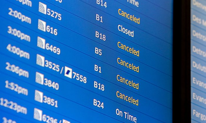 Flight boards at O'Hare International Airport show cancellations in Chicago on Jan. 22, 2016. Airlines at Chicago's two major airports have canceled 215 flights largely due to a blizzard threatening down on the East Coast. (AP Photo/Teresa Crawford)