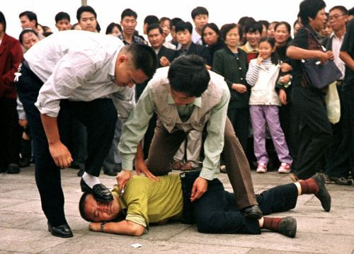 Chinese police violently detain a practitioner of the spiritual discipline Falun Gong on Tiananmen Square in Beijing on Oct. 1, 2000. (AP Photo/Chien-min Chung)