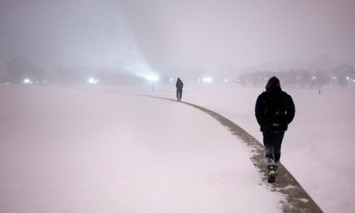 People use a wall surrounding the Washington Monument to walk above the snow after a snowstorm in Washington, D.C., on Jan. 23, 2016. (Brendan Smialowski/AFP/Getty Images)
