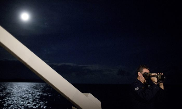 A Greek Coast Guard officer looks through night vision binoculars during a patrol at the Aegean sea near the Greek island of Chios on Jan. 20, 2016. Greek coast guard patrol vessels and lifeboats reinforced by the European Union's border agency Frontex ply the waters of the eastern Aegean Sea along the frontier with Turkey, on the lookout for people being smuggled onto Greek islands, the frontline of Europe's massive refugee crisis. (AP Photo/Petros Giannakouris)