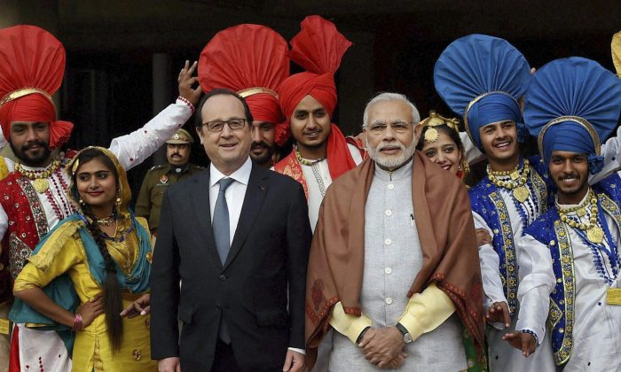 French President Francois Hollande, center left, and Indian Prime Minister Narendra Modi, center right, pose for a group photo with Indian folk dancers at the government museum and art gallery in Chandigarh, India, Sunday, Jan. 24, 2016. (Manvender Vashist/Press Trust of India via AP)