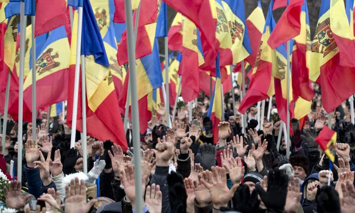 People raise their hands during a large protest in Chisinau, Moldova, on Jan. 24, 2016. More than 15,000 people gathered to protest against the government, demanding early elections in the impoverished East European nation, an action that comes after demonstrators stormed Parliament last week as lawmakers approved a new pro-European government. (AP Photo/Vadim Ghirda)