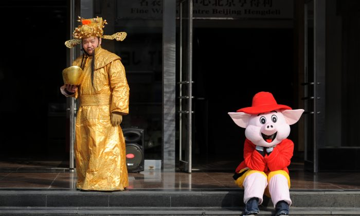 A sales man (L), dressed as the god of wealth, waits for customers with his partner (R) dressed as a cartoon character at the entrance of a shop in Beijing on March 22, 2013. (Wang Zhao/AFP/Getty Images)