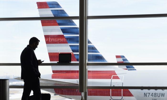 Ryan Parks of Arlington, Va., talks on the phone as he waits for his flight to Boston at Washington's Ronald Reagan National Airport, on Jan. 25, 2016.  (AP Photo/Susan Walsh)