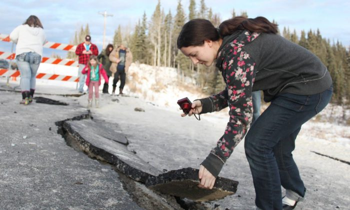 Tyrrel Corveia, 14, lifts a piece of the road surface along a crack in Kalifornsky-Beach Road near Kasilof, Alaska, Sunday, Jan. 24, 2016, following a magnitude-7.1 earthquake. Corveia lives in a yurt and said she woke up to the structure shaking on its stilts, but said the home sustained no damage. (Kelly Sullivan/Peninsula Clarion via AP)
