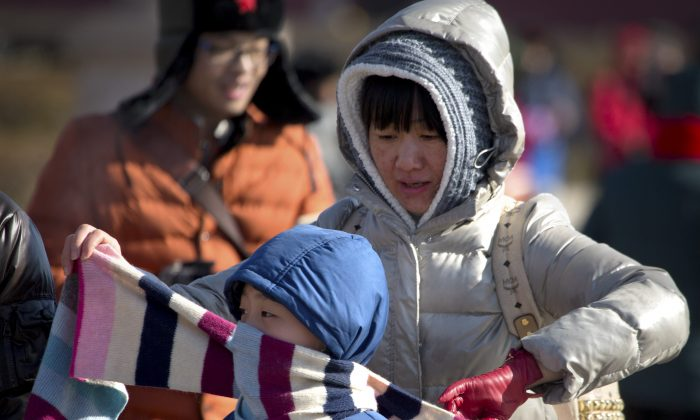 A woman ties a scarf around a boy's face in front of Tiananmen Gate near Tiananmen Square in Beijing, Saturday, Jan. 23, 2016. (AP Photo/Mark Schiefelbein)