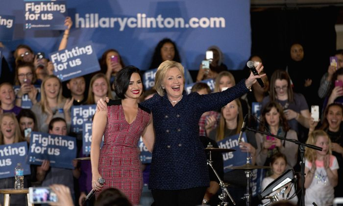 Democratic presidential candidate Hillary Clinton and musician Demi Lovato acknowledge the cheering crowd at a rally on the campus of University of Iowa in Iowa City, Iowa, on Jan. 21, 2016. Hillary Clinton has a lot of celebrity pals on her side, like singers Katy Perry or Demi Lovato. It's a play to help the former secretary of state connect with younger voters. But so far, the star power isn't swaying the college set. Instead, they prefer a rumpled 74-year-old who eschews a Hollywood opening act. (AP Photo/Jae C. Hong)