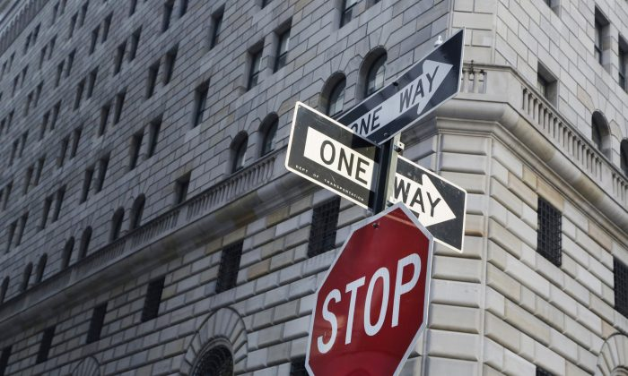 One way signs and a stop sign are posted in the financial district in front of the Federal Reserve Bank of New York on Jan. 15, 2016. (AP Photo/Mark Lennihan)