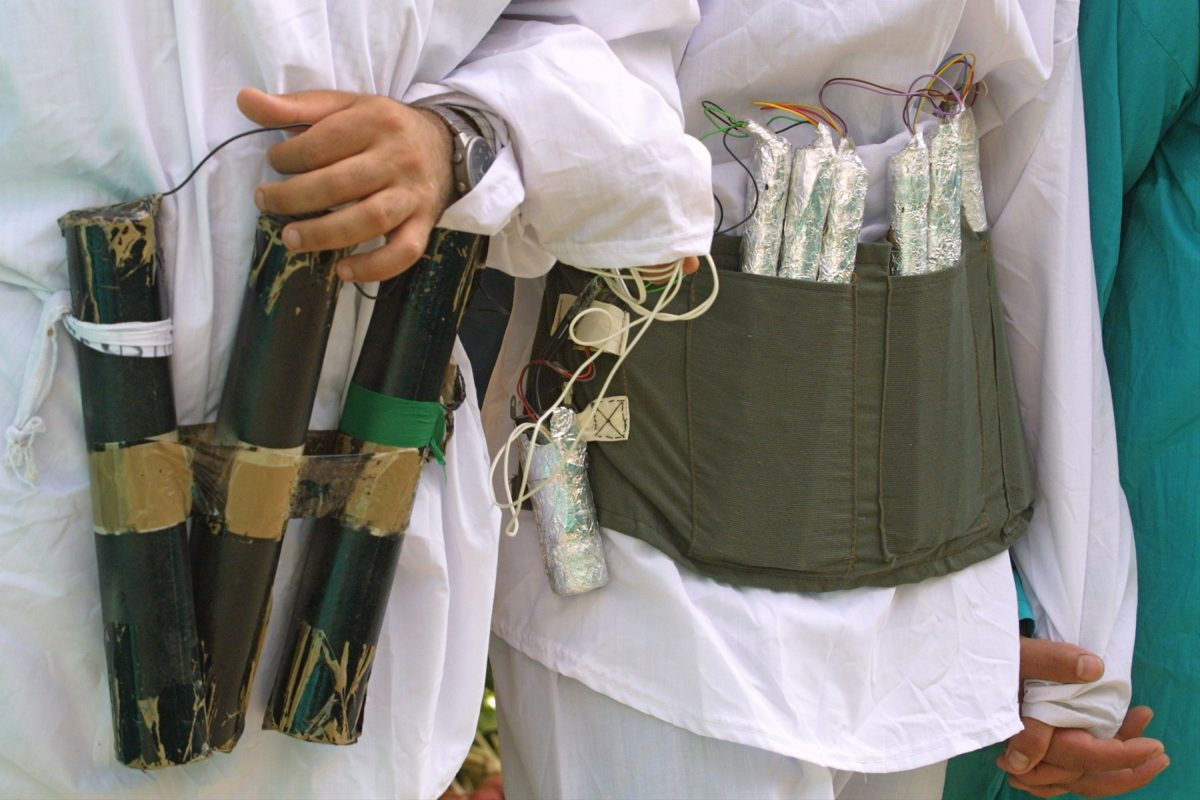"""Hamas militants, dressed as a """"martyr,"""" plays with a mock up of a suicide-bomber's """"belt of explosives"""" during the funeral of their leader Abdel Rahman Hamad in the West Bank town of Qalqilya, on Oct. 14, 2001. (David Silverman/Getty Images)"""