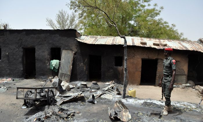 An anti-riot policeman stands in front of a burnt house in Gubio in Borno State, northeast Nigeria, on May 26, 2015. (Stringer/AFP/Getty Images)