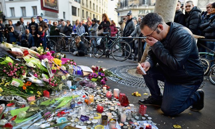 A man weeps as he lays flowers down at the La Belle Equipe restaurant on Rue de Charonne following the terrorist attacks in Paris on Nov. 15, 2015. (Jeff J Mitchell/Getty Images)