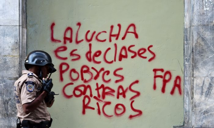 "A policeman walks past a graffiti reading ""The fight is of poor and rich classes"" outside the National Assembly ahead of Venezuelan president Nicolas Maduro's presentation of the annual report before the opposition controlled parliament in Caracas on Jan. 15, 2016. (Ronaldo Schemidt/AFP/Getty Images)"