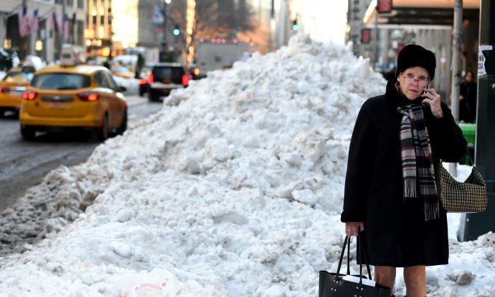 People try to navigate through the snow on Park Avenue on Jan. 25, 2016 as New Yorkers return to work after the city was hit with a record-setting snowfall. (Timothy A. Clary/AFP/Getty Images)
