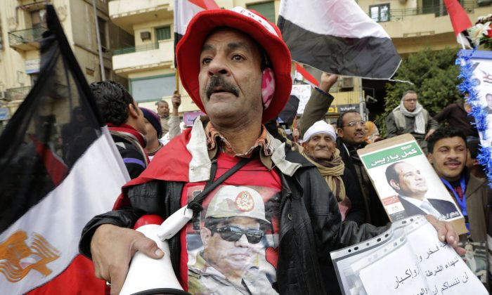 A small number of supporters of Egyptian President Abdel Fattah el-Sissi wave posters and national flags as they mark Police Day, which falls on Jan. 25, the anniversary of the 2011 uprising, in Tahrir Square, Cairo, Egypt, Monday, Jan. 25, 2016.  (AP Photo/Amr Nabil)