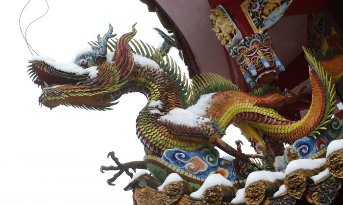 Snow sits on the decorative dragons at the Pinglin temple in the high mountain area of New Taipei City, Taiwan, Monday, Jan. 25, 2016. (AP Photo/Wally Santana)