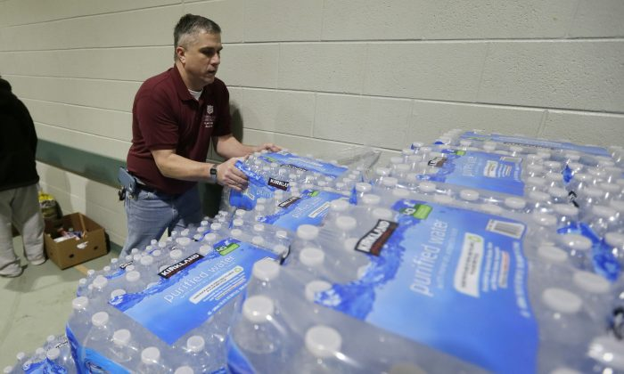 Jack Huffman of the Salvation Army helps carry bottled water at the Salvation Army Flint Beecher Corps Community Center in Flint, Mich., Tuesday, Jan. 26, 2016. On top of millions of dollars in pledged governmental aid, faith-based and nonprofit organizations, companies large and small, the rich and famous, and many other individuals all have targeted Flint for significant charitable giving — in the form of money and millions of bottles of water.  (AP Photo/Carlos Osorio)