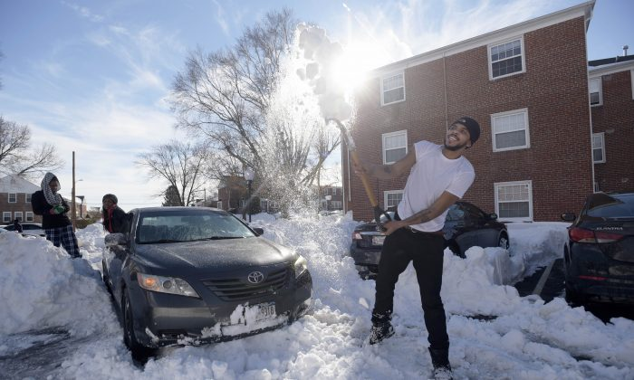 Mike Roach, right, of New York, a junior at Towson University, clears snow from his car after getting stuck in Towson, Md., Monday, Jan. 25, 2016. (AP Photo/Steve Ruark)