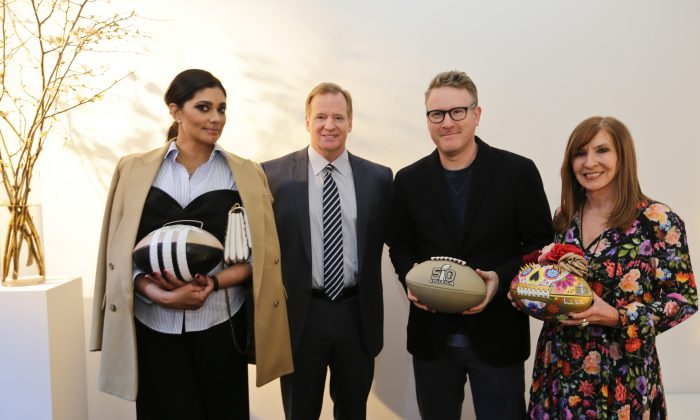 Fashion designers Rachel Roy, left, Nicole Miller (R) and Todd Snyder, second from right, pose for photographs with NFL Commissioner Roger Goodell at the unveiling of the CFDA footballs, Wednesday, Jan. 20, 2016, at NFL headquarters in New York. (AP Photo/Frank Franklin II)