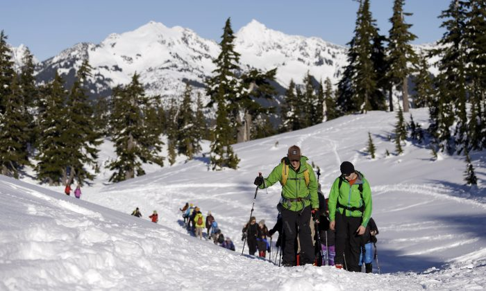 In this Jan. 11, 2016, photo Eric Gullickson, front left, an avalanche instructor with the Northwest Avalanche Center, leads teenagers on an avalanche awareness field trip at Mount Baker, Wash. (AP Photo/Elaine Thompson)