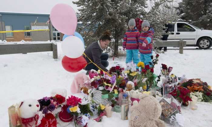 Tashina Montgrand lays flowers outside the La Loche Community School as her daughters look on, Jan. 25, 2016. The Saskatchewan community is struggling to recover after a shooting that left four dead and seven wounded. THE CANADIAN PRESS/Jonathan Hayward