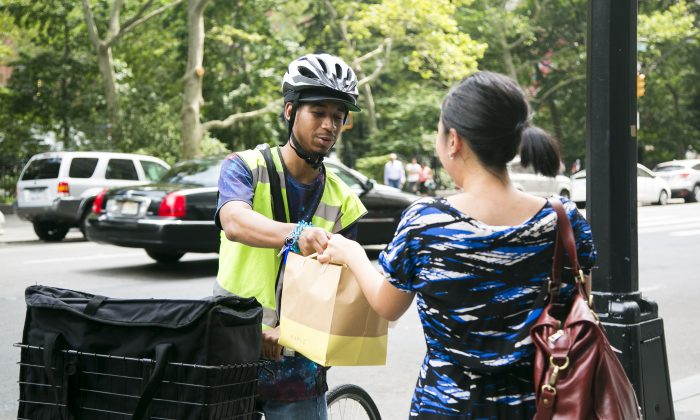 Isaiah delivers food from Maple, a meal delivery service, in the Financial District in Manhattan, New York, on July 20, 2015. (Samira Bouaou/Epoch Times)