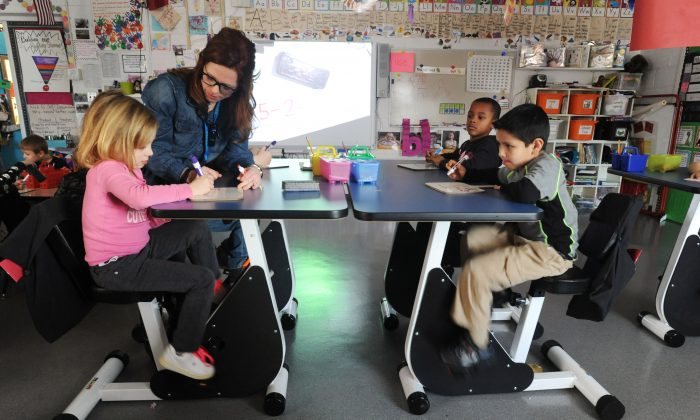 In this photo taken on Tuesday, Jan. 19, 2016, Estes Elementary School kindergarten students Evelyn Bolmer, 5, front left, Jase Bellamy, 6, back right, and Eric Guarneros, 6, front right, listen as their teacher Faith Harralson assists Bolmer with a math equation as they ride pedal desks in Owensboro, Ky. Harralson won a $12,000 grant from the school system to install the desks in her classroom. (Jenny Sevcik /The Messenger-Inquirer via AP)