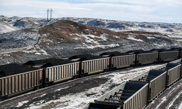Rail cars are filled with coal and sprayed with a topper agent to suppress dust at Cloud Peak Energy's Antelope Mine north of Douglas, Wyo., on Jan. 9, 2014. (Ryan Dorgan/Casper Star-Tribune via AP)