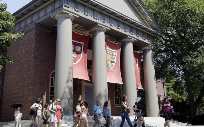 A tour group walks through the campus of Harvard University in Cambridge, Mass., Aug. 30, 2012. (AP Photo/Elise Amendola)