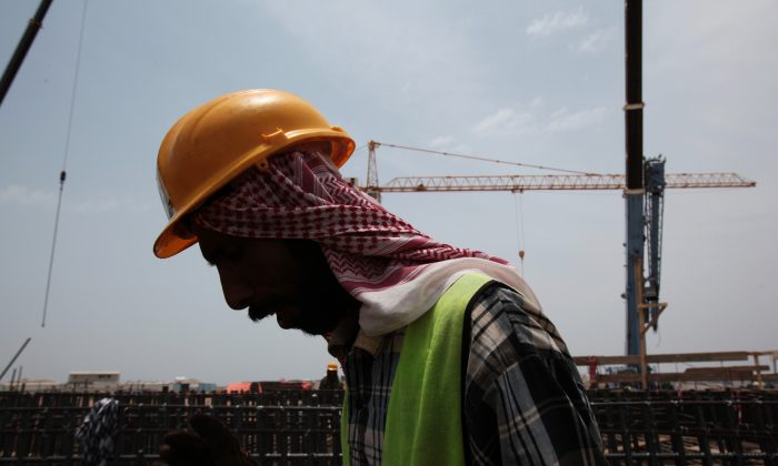 A man works on construction of the Kingdom Tower, a planned 252-story building, which aims to become the world's tallest skyscraper when complete, in Jiddah, Saudi Arabia, on May 8, 2014. Saudi Arabia is racing to attract more investment and overhaul its economy as low oil prices expose it to urgent domestic challenges. (AP Photo/Hasan Jamali)