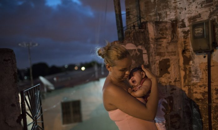 Gleyse Kelly da Silva, 27, outside her home in Recife, Brazil, on Jan. 27, 2016, holds her daughter Maria Giovanna who was born with microcephaly. (AP Photo/Felipe Dana)