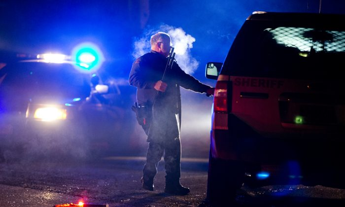 A Oregon State police officer stands by a vehicle as police officers block Highway 395 in Seneca, Ore., Tuesday, Jan. 26, 2016. (Dave Killen/The Oregonian via AP)