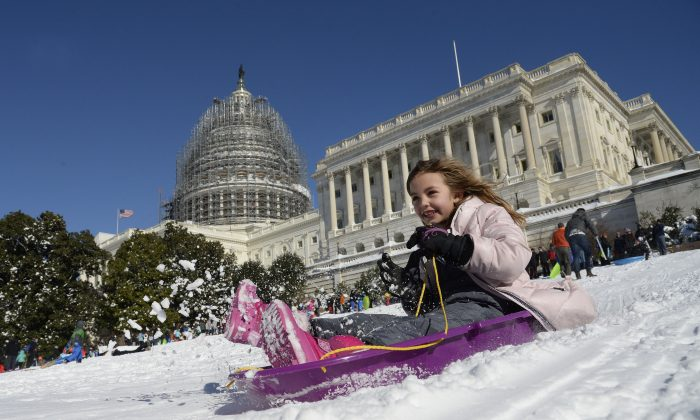 """A young girl is sliding on the West Lawn of the US Capitol on Jan 24, 2016. The storm – dubbed """"Snowzilla"""" – killed at least 47 people after it walloped several states over 36 hours on Friday and Saturday, affecting an estimated 85 million residents who were told to stay off the roads and hunker down in doors for their own safety. (OLIVIER DOULIERY/AFP/Getty Images)"""
