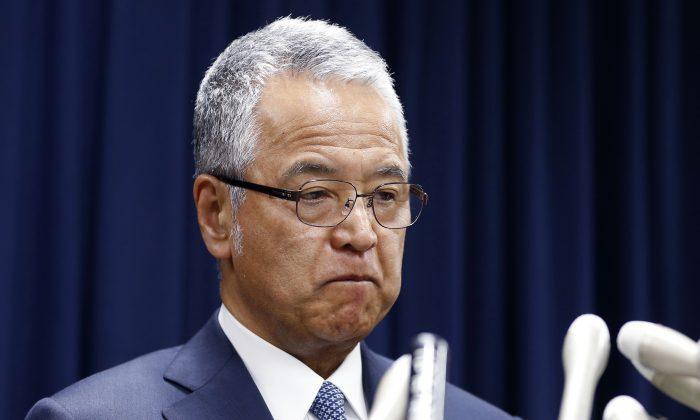 Japanese Economy Minister Akira Amari bites his lips during a nationally televised news conference in Tokyo, Thursday, Jan. 28, 2016. (AP Photo/Shizuo Kambayashi)