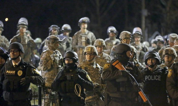 In this Friday, Nov. 28, 2014, file photo, police and Missouri National Guardsmen face protesters gathered in front of the Ferguson Police Department in Ferguson, Mo. (AP Photo/Jeff Roberson)