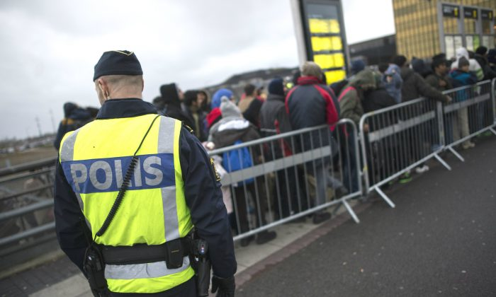 A policeman watches over a queue of newly arrived people at Hyllie Station, outside Malmo, Sweden, on Nov. 19, 2015. (Johan Nilsson/TT News Agency via AP)