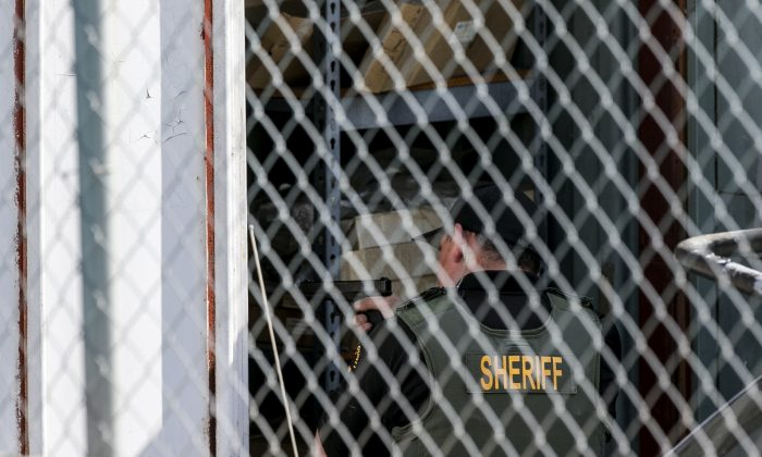 A Orange County Law enforcement agent points his gun inside a container while conducting a search for additional suspects at the back of an auto electric shop garage in Santa Ana, Calif., on Friday, Jan. 29, 2016.  (AP Photo/Damian Dovarganes)