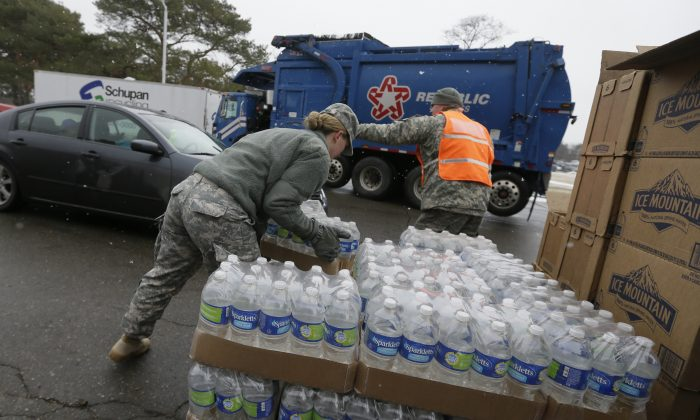 Members of the Michigan National Guard load bottled water at a fire station, Thursday, Jan. 28, 2016 in Flint, Mich. (AP Photo/Carlos Osorio)