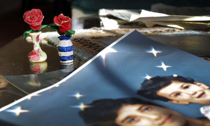 Prison artwork created by Adnan Syed sits near family photos in the home of his mother, Shamim Syed, Wednesday, Dec. 10, 2014, in Baltimore. (AP Photo/Patrick Semansky)