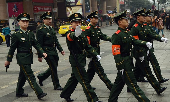 Chinese paramilitary police marching through the downtown shopping area of Chongqing in February 2013. Chinese authorities recently indicted a Canadian for allegedly stealing state secrets. (Mark Ralston/AFP/Getty Images)