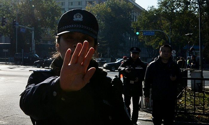 Chinese police try to stop photos being taken in Beijing on Nov. 12, 2013. (Mark Ralston/AFP/Getty Images)