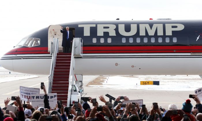 Republican presidential candidate Donald Trump waves as he arrives on his plane at a campaign event at Dubuque Regional Airport, Saturday, Jan. 30, 2016 in Dubuque, Iowa. (AP Photo/Paul Sancya)
