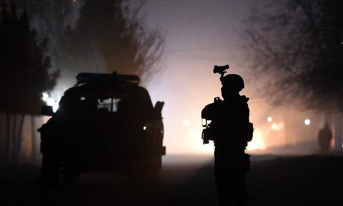 An Afghan security official stands as he keep watch at the site of a suicide car bomb attack at a French restaurant, Le Jardin, in Kabul on Jan. 1, 2016. (Wakil Kohsar/AFP/Getty Images)