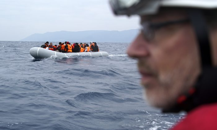 """A German rescuer volunteer escorts with his vessel a dinghy with refugees and migrants as they arrive from the Turkish coast to the northeastern Greek island of Lesbos, on Jan. 29, 2016. A migration monitoring agency says deaths of refugees and migrants crossing the Aegean Sea between Turkey and Greece are """"increasing at an alarming rate"""" as 218 people have died in January on that eastern Mediterranean route. (AP Photo/Mstyslav Chernov)"""