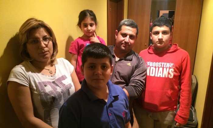 """Syrian refugee Maher al-Masihi (2R) and his family pose for a photo in Murmansk, Russia, on Jan. 28, 2016. When al-Masihi and his family set out four months ago, they planned on traveling to Norway via Russia to avoid the """"risky"""" Mediterranean sea crossing. Now, the family of five is stranded in the Russian Arctic city of Murmansk, held up by bureaucracy and border control. (AP Photo/Roman Stepanovich)"""